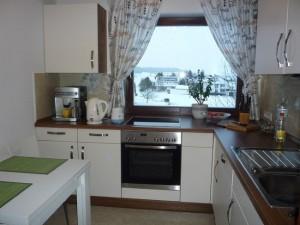 1-bucatarie moderna cu blat de lucru si plita sub fereastra
