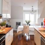 10-bucatarie cu mobila alba proiectata pe doua laturi si pereti placati cu panouri din sticla rosie