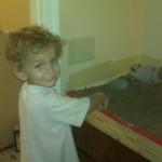 10-mezinul familiei ajutand la turnarea blatului din beton din bucatarie