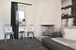 12-doua scaune langa semineu decorativ in coltul livingului apartamentului modern