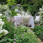 12-mobilier din fier forjat alb asezat in mijlocul unei gradini cu flori albe