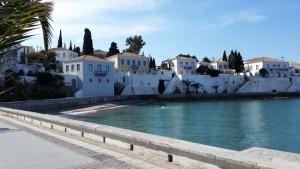 13-case vechi cu ziduri inalte din piatra pe faleza din Spetses