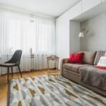 2-canapea inconjurata de dulapuri albe zona de living a garsonierei de 33 mp