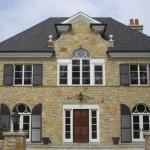 2-casa stil clasic cu fatada placata cu piatra tamplaria alba si obloane si acoperis gri petrol