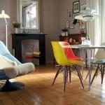 2-scaune-colorate-eames-in-jurul-unei-mese-rotunde-de-sticla