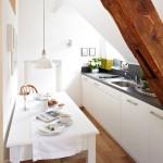 3-bucatarie ingusta cu mobila alba si loc de luat masa amenajat pe peretele opus blatului de lucru