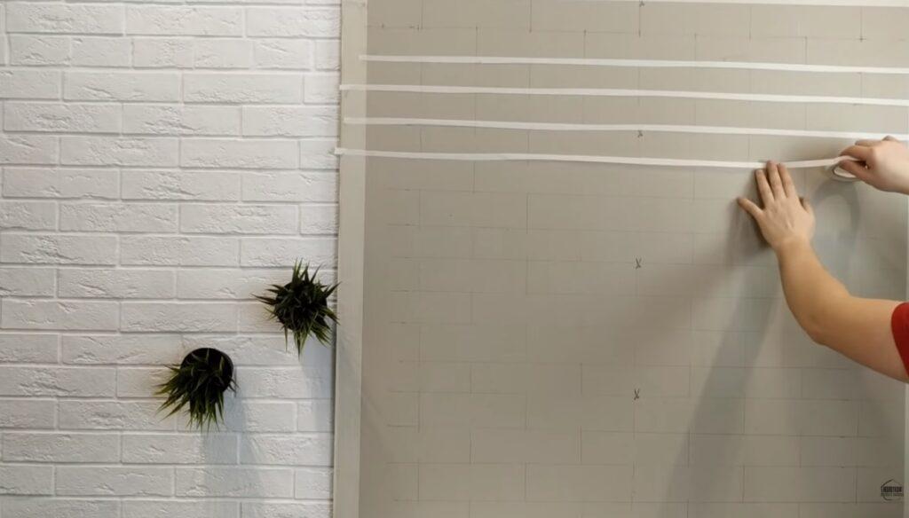 aplicare banda adeziva hartie pe dungile trasate pe perete