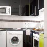 5-mobilier pe colt de culoare neagra in decorul bucatariei deschise spre living
