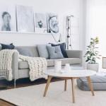 5-tablouri in alb negru montate pe o polita din spatele canapelei din living