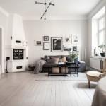 7-living scandinav cu semineu si cu galerie de tablouri pe peretele cu canapeaua