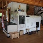 7-soba cu plita cuptor si pat montata in centrul unei bucatarii open space