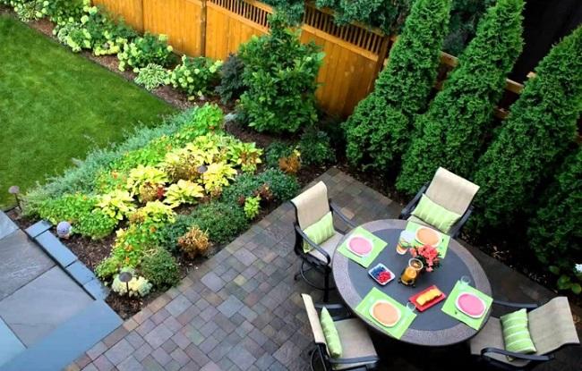 8-loc de luat masa amenajat intr-o curte mica cu spatiu verde si portiuni pavate