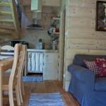 8-loc de luat masa amenajat intre zona de living si bucataria casei mici din barne de lemn