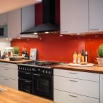 9-bucatarie moderna cu mobila alba si pereti placati cu panouri din sticla colorata rosie