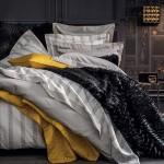 9-pat din dormitor aranjat cu multe perne si cuverturi moi asortate