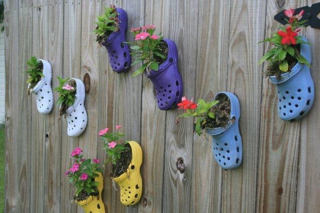 aranjament decorativ pentru gard din flori plantate in papuci de cauciuc