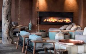 canapele si fotolii in fata semineului de pe terasa cabana de lux africa de sud