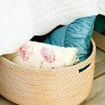 cos rotund impletit pentru pastrarea penutelor decorative sub patul din dormitor
