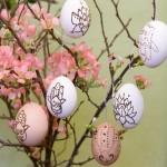 decoratiune de paste oua colorate agatate in crenguta inflorita