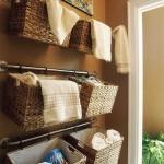 etajere din cosuri impletite agatate de bara metalica fixata de perete baie
