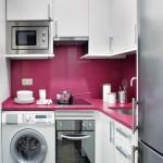 exemplu amenajare bucatarie foarte mica si ingusta mobila alba perete placat cu panou sticla roz