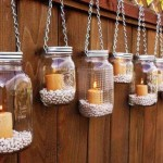 iluminat decorativ gradina lumanari aprinse in borcanase agatate cu lanturi de gard
