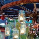 lustra iluminat exterior handmade din roata lemn si borcane goale cu lumanari in interior